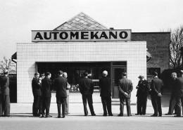 Bilden visar män i kostym som tittar på en verkstad. Kanske tagen på 50-talet.