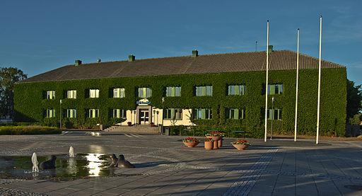 Bilden visa Ifö Sanitärs huvudkontor i Bromölla, en byggnad täckt med växtlighet. Framför huset finns ett torg med en fontän.